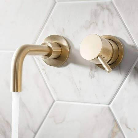 Gold tap of white tiled wall